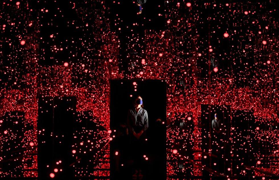 Lundi, un employé de la galerie Tate Modern de Londres pose dans l'installation 'Infinity Mirrored Room' de l'artiste japonais Yayoi Kusama à Londres, au Royaume-Uni.  Le Royaume-Uni autorise à nouveau les voyages à l'étranger, l'une des principales mesures de désescalade, qui comprend également la réouverture d'hôtels couverts ainsi que de musées, au détriment de l'avancée inquiétante de la variante indienne du virus.