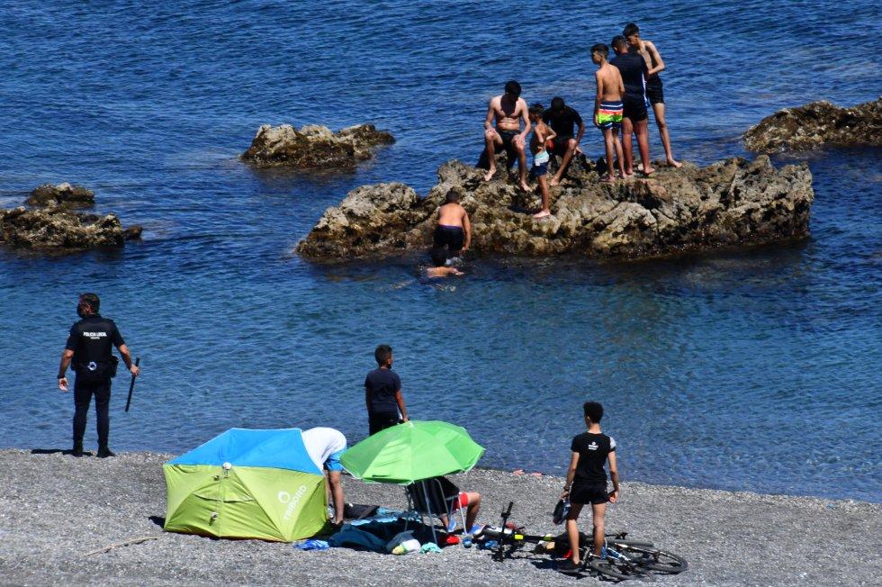 Os efetivos policiais não deram abasto e mais de uma centena de jovens entraram em Ceuta pela zona do Tarajal sem problemas. Na imagem, um agente da policial local vigia vários imigrantes, na segunda-feira.