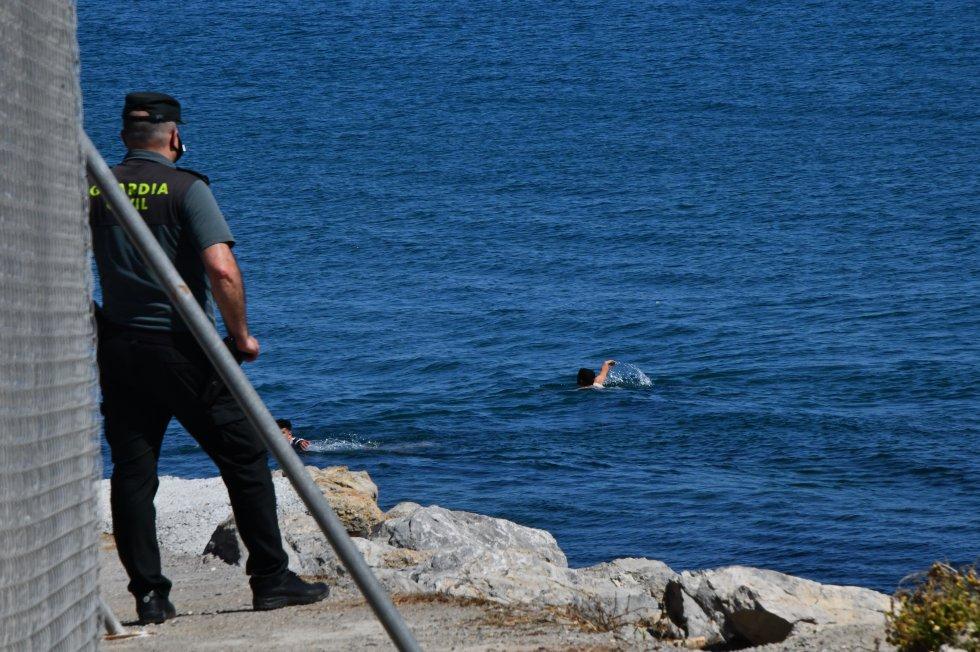 Um agente da Policia civil observa d como vários jovens cruzam a nado para o território espanhol, na segunda-feira.