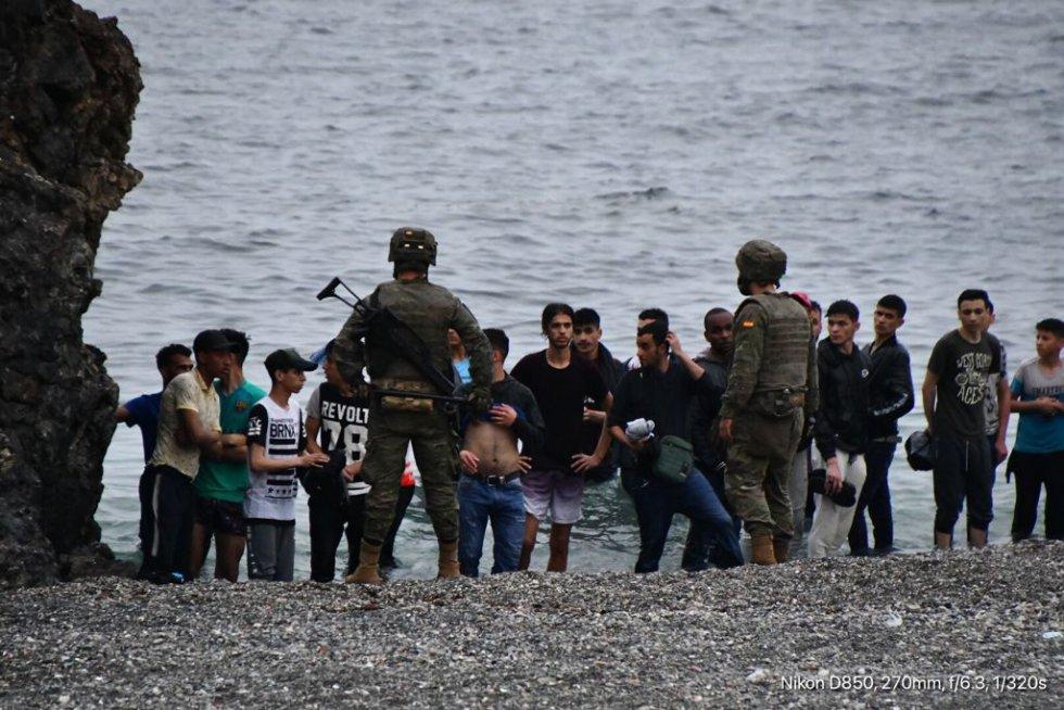 Militares controlam um grupo de imigrantes que chegaram a nado nos quebra-mares da fronteira de Ceuta, nesta terça-feira. Nas últimas 24 horas, milhares de jovens, mas também famílias inteiras, se lançaram ao mar ante a passividade das autoridades marroquinas. Entre os recém-chegados calcula-se que há cerca de 1.500 menores de idade. Um homem morreu na tentativa.