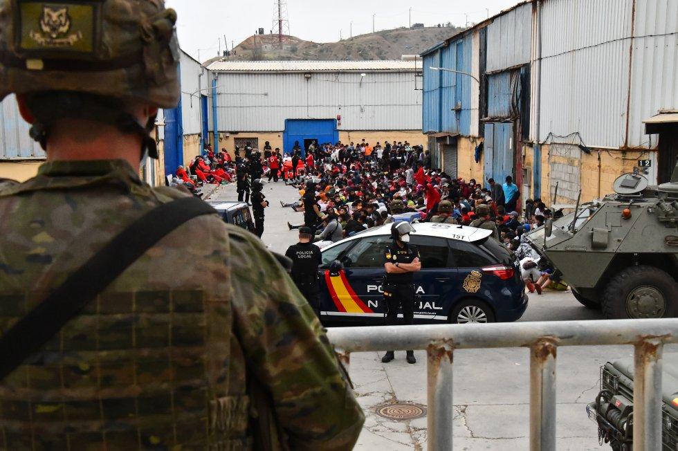 Agentes do Policial Nacional e militares vigiam centenas de imigrantes depois de sua chegada nesta terça-feira a Ceuta, nesta terça-feira.