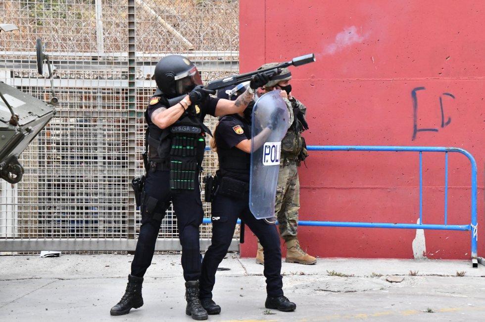 Um agente da Policial Nacional lança bombas de fumaça no perímetro da cidade de Ceuta, nesta terça-feira.