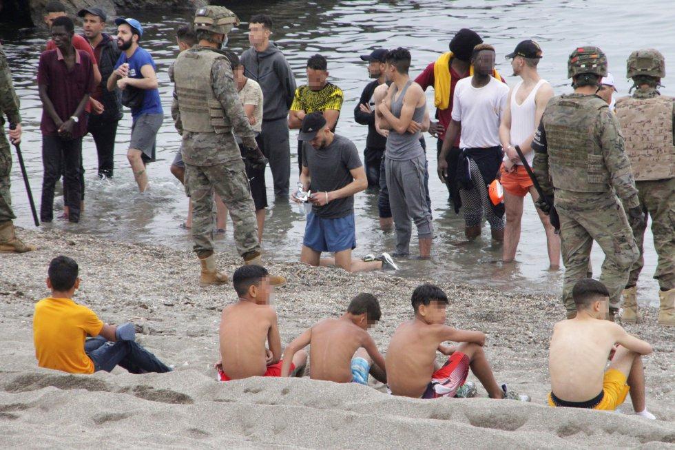 Na praia do Tarajal, há grupos de jovens de pé, na água, em frente aos militares, que formaram um cordão na orla.