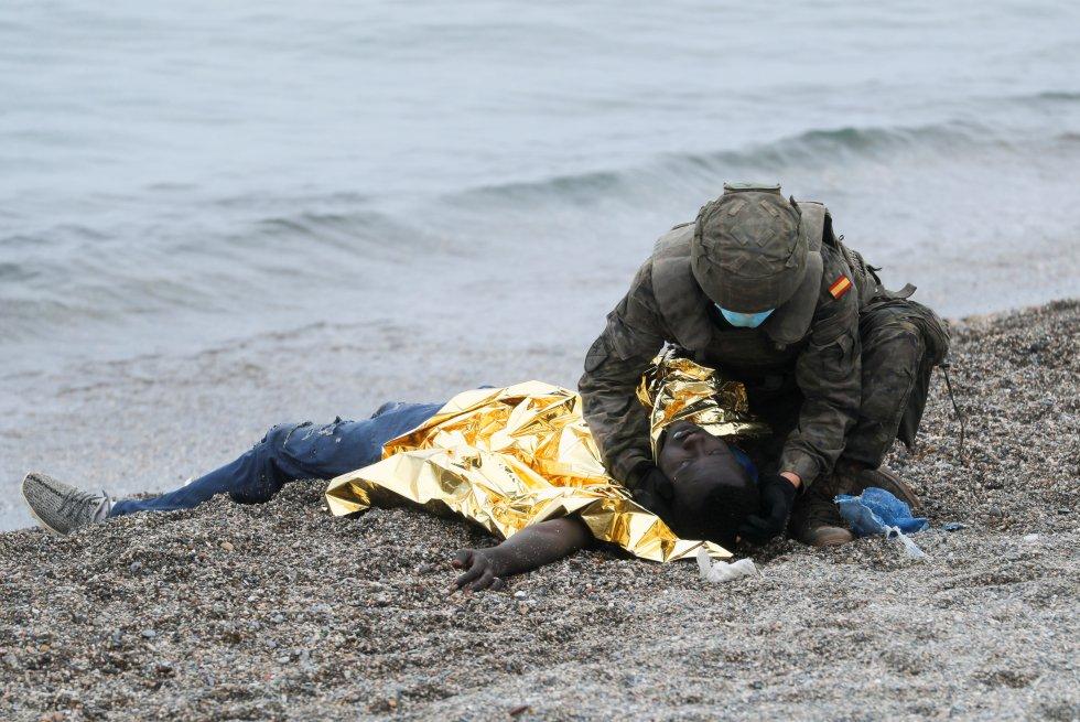 Um soldado do Exército ajuda um imigrante que conseguiu atravessar um dos quebra-mares de Ceuta, nesta terça-feira. A chegada de pessoas nadando e a pé foi constante durante toda a segunda-feira e continua na manhã desta terça-feira.