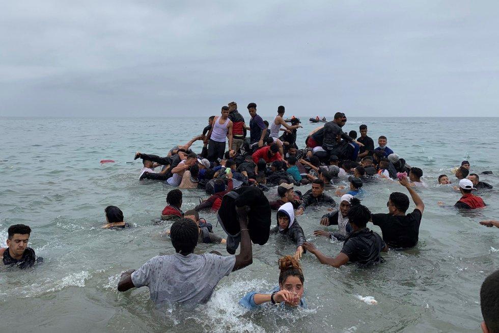 Um grupo de pessoas assumem uma embarcação das autoridades marroquinas na praia da localidade de Fnideq (Castillejos) para cruzar os quebra-mares de Ceuta, nesta terça-feira. O Exército se dirigiu dirigiu aos navios do Tarajal, onde se concentrava a boa parte dos imigrantes, principalmente os menores de idade. Também levaram veículos blindados à praia do Tarajal.