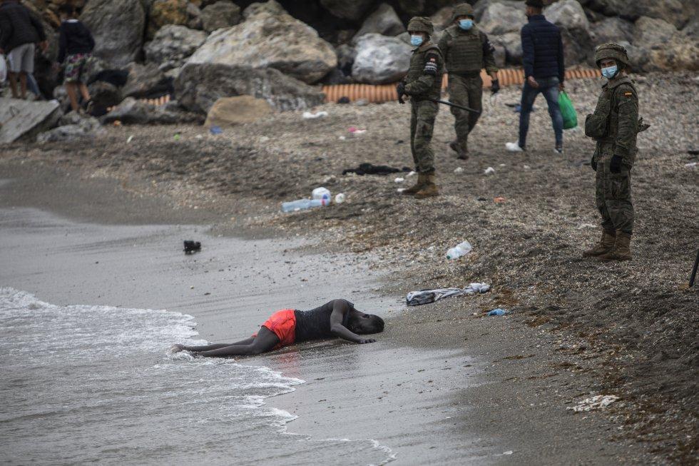 Um homem permanece deitado na praia enquanto o Exército isola a zona, nesta terça-feira.