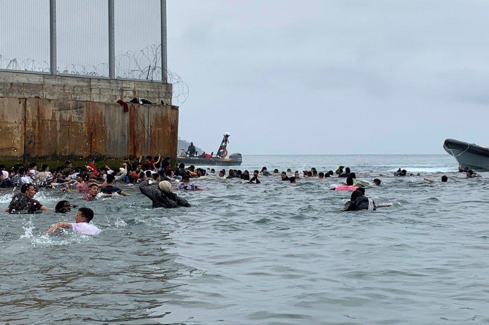 Um grupo de pessoas tentam chegar nadando desde a praia da localidade de Fnideq (Castillejos, Marrocos) para um dos quebra-mares de Ceuta, nesta terça-feira.