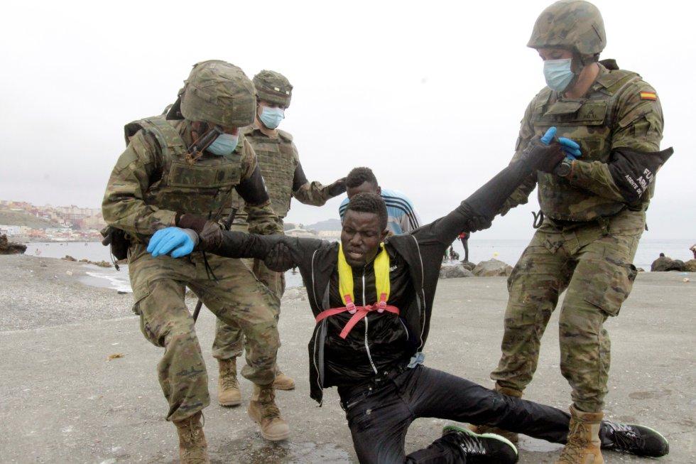 Membros do Exército ajudam um imigrante que conseguiram cruzar a fronteira para Ceuta, nesta terça-feira.