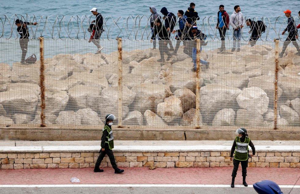 Agentes de segurança marroquinos monitoram grupo de imigrantes que caminham pela costa na cidade de Fnideq, em uma tentativa de cruzar a fronteira de Marrocos para Ceuta, na Espanha.