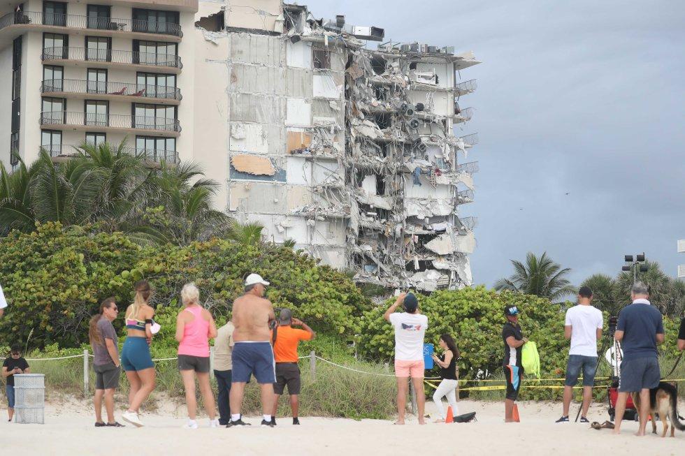 Un grupo de personas observan los daños causados por el derrumbe parcial del edificio.