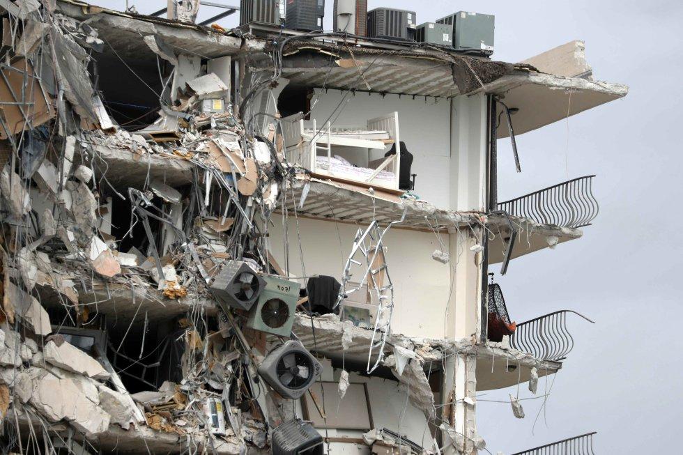Objetos y escombros cuelgan de una sección del condominio Champlain Towers South, tras el derrumbe parcial del edificio, en el área de Surfside de Miami.