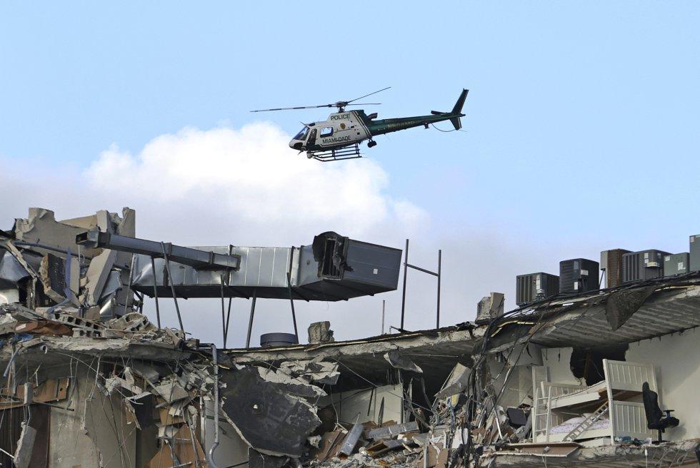Un helicóptero sobrevuela los restos del edificio, este jueves. El alcalde de Surfside, Charles Burckett, confirmó en una rueda de prensa que una de las primeras personas rescatadas murió al llegar al hospital y subrayó que es posible que haya más muertos, pues la parte este del edificio se derrumbó planta sobre planta y puede haber personas aplastadas entre las capas.