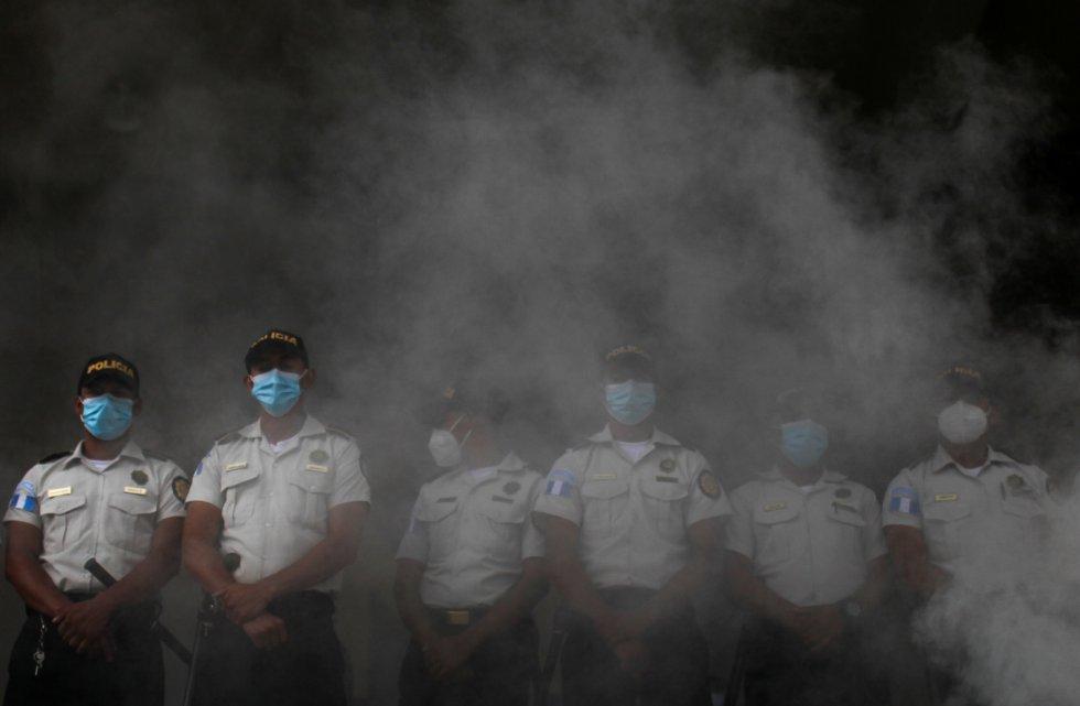 Agentes de policía en medio del humo de neumáticos quemados afuera del edificio del Ministerio Público durante las protestas en la Ciudad de Guatemala.
