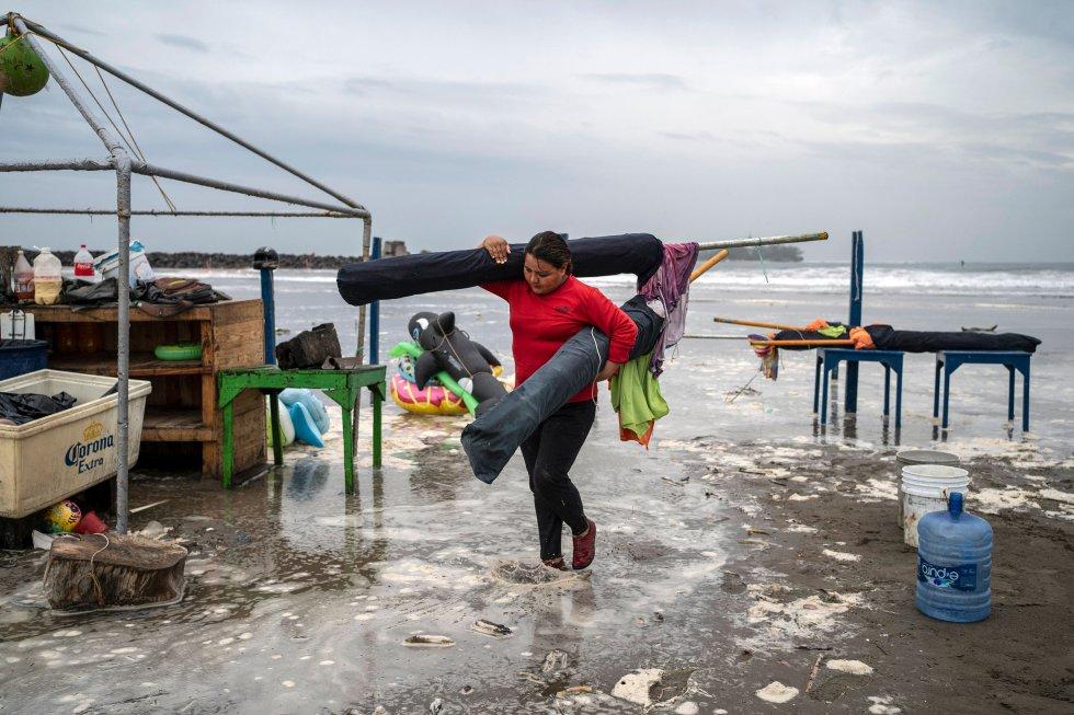 Una mujer quita sombrillas de la playa mientras las fuertes olas llegan a la costa debido al huracán 'Grace'.