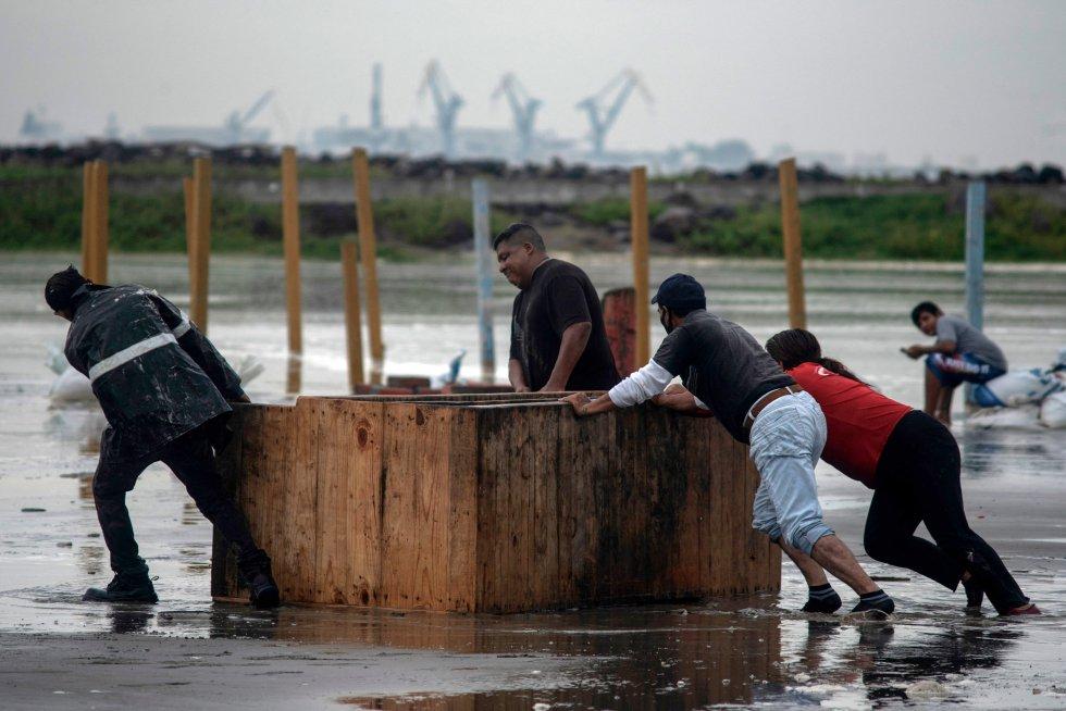 Tabajadores retiran sus pertenencias de la playa ante el fuerte oleaje de la costa.