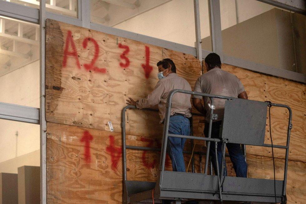 Trabajadores colocan tablas de madera en las ventanas de un supermercado para evitar los daños que pueda provocar 'Grace'. Las autoridades alertan a la población para que se prepare en caso de una posible evacuación, por lo que se han activado 217 inmuebles que funcionarán como refugios temporales en el Estado.