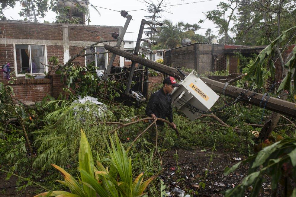 Un hombre inspecciona los daños después de que parte de su casa fuera derribada por los vientos provocados por el huracán 'Grace', en Tecolutla, estado de Veracruz este sábado.