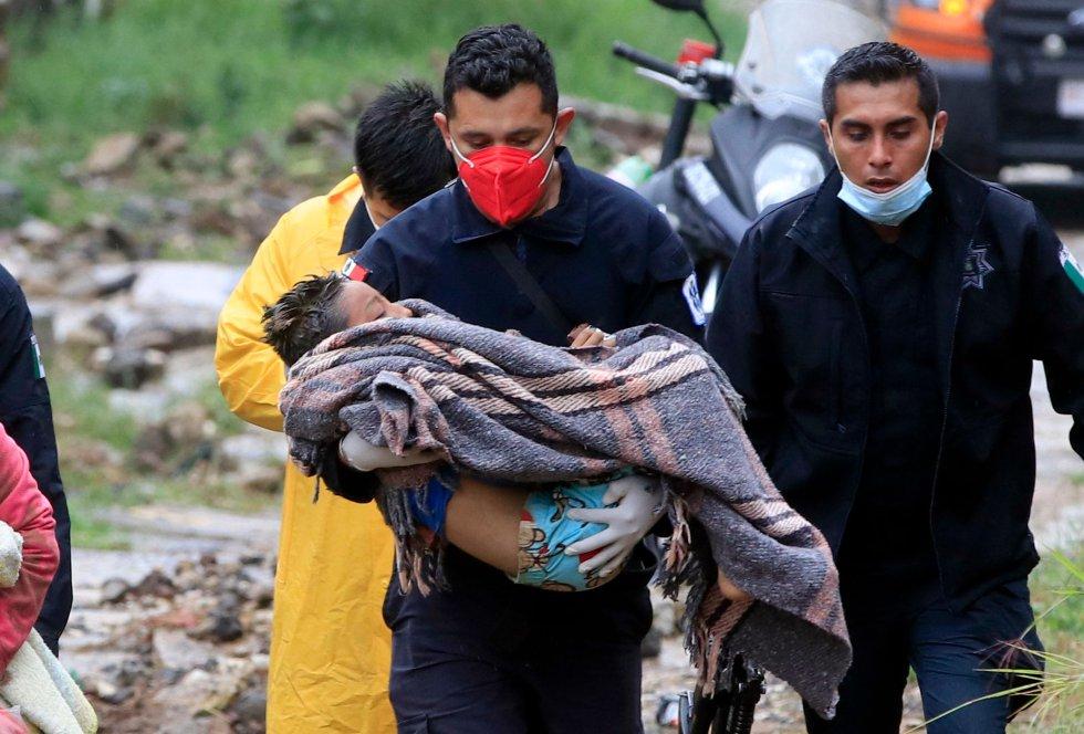 Un paramédico de seguridad pública lleva a un niño luego de que un deslizamiento de tierra de una colina aplastara una casa debido al paso del huracán Grace, en el barrio Loma Bonita en Xalapa.