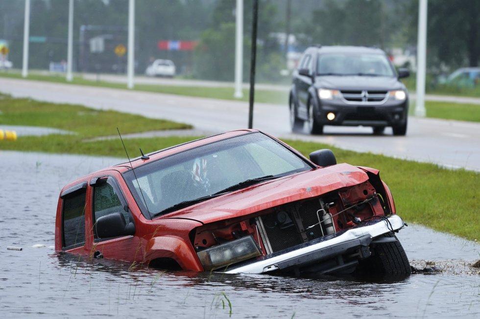 Un vehículo abandonado se ha sumergido en una zanja junto a una carretera inundada en Bay Saint Louis, Mississippi