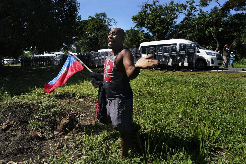 Un migrante haitiano sostiene la bandera de su país mientras suplica a la Guardia Nacional de México que no detenga a los migrantes que se dirigen a la frontera entre Estados Unidos y México.