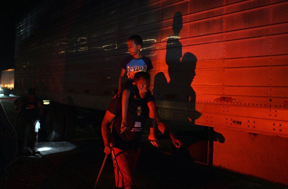 """Un migrante viaja con un niño en sus hombros en Macastepec, Chiapas. Pese a ser calificados despectivamente como """"sin papeles"""", miles de migrantes acarrean carpetas completas con sus expedientes e historias de vida para presentar a las autoridades migratorias primero y después, a la Comisión Mexicana de Ayuda al Refugiado (COMAR)."""