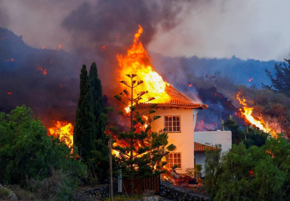 La erupción en el volcán de La Palma continúa este lunes, después de que el domingo comenzara a arrojar fuego y ceniza. En la imagen, una casa se quema al ser alcanzada por la lava del volcán en Los Llanos de Aridane, este lunes.