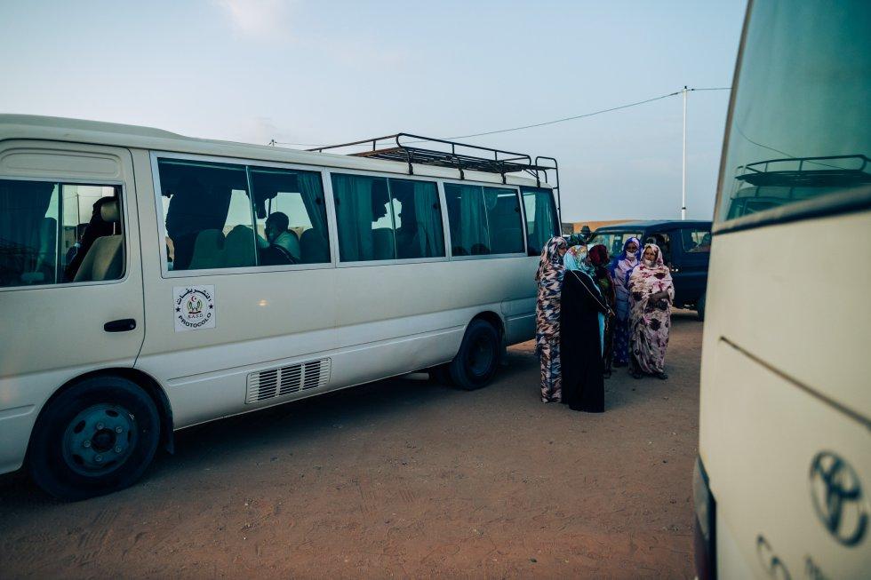 Un grupo de anfitrionas espera junto a los autobuses la llegada de los visitantes para distribuirlos en sus alojamientos, sus propias casas, en Bojador.