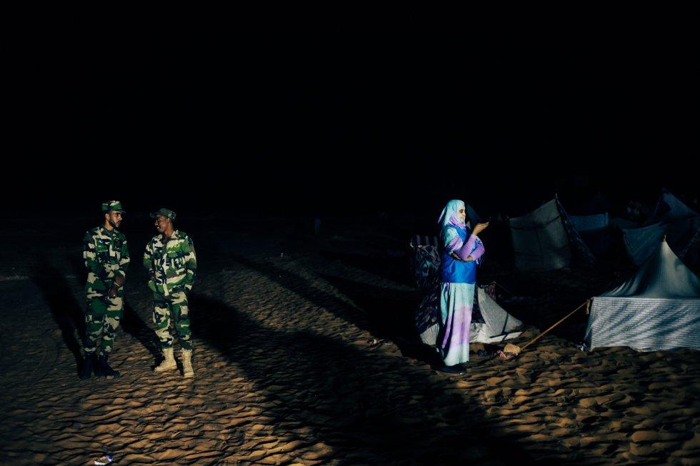 Una voluntaria de la organización de las celebraciones en Dajla y fuerzas de seguridad junto a las recreaciones de jaimas que van a ser quemadas en conmemoración del desalojo de Gdeim Izik, un campamento de protesta a pocos kilómetros de El Aaiún, la ciudad más importante del Sahara Occidental, en noviembre de 2010.