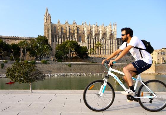 un joven circula con su bicicleta junto a la catedral de palma