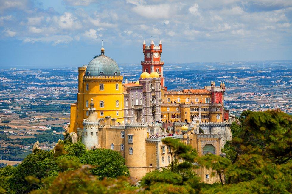 Su colorida silueta es uno de los iconos de Sintra, villa cercana a Lisboa. Su romántica imagen, con su singular mezcla de estilos y corrientes estéticas que roza lo extravagante, está hecha a golpe de azulejos típicamente portugueses, motivos mudéjares y manuelinos integrados con torres góticas, mobiliario barroco. Lo mandó construir en el siglo XIX el rey Fernando II, sobre las ruinas de un monasterio de frailes jerónimos, como regalo para su esposa María II de Portugal. Está encaramado a una montaña, por cuyas laderas se extiende un parque inglés con miles de especies botánicas procedentes de todo el planeta.