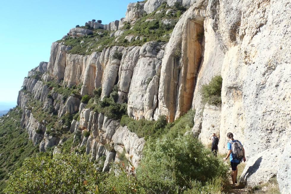 Los 'graus' que surcan la sierra del Montsant, como el de l'Escletxa (en la foto), son caminos estrechos que ganan altura de forma abrupta y directa. El más vertiginoso es el de Barrots (5,5 kilómetros, dificultad media-alta), que discurre por terrazas colgadas de estas grandes paredes, asomándose al vacío sobre los viñedos del Priotat.