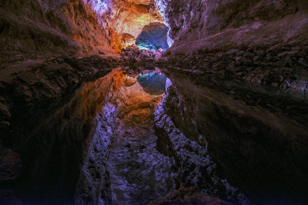 Un espejismo aguarda al final de la cueva de los Verdes, el tubo de lava de siete kilómetros de largo que abrió hace cinco mil años en la isla canaria de Lanzarote la erupción del volcán Corona. El itinerario que la recorre hoy enlaza tres galerías superpuestas y llega hasta el lago de la foto, donde el reflejo de la bóveda de piedra sobre el agua hace que parezca una sima inmensa.