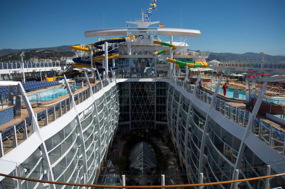 Cubierta del 'Symphony of the Seas', con tres toboganes de agua así como piscinas, jacuzzis y hamacas a ambos lados de la embarcación.