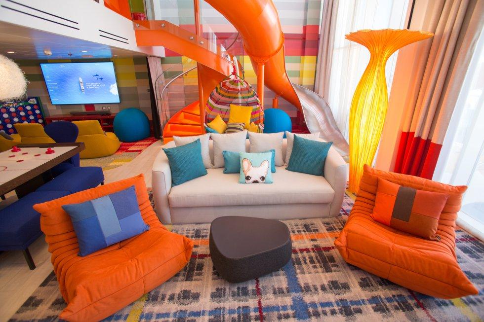 Toboganes, lámparas de diseño, sofás y butacas son parte de la decoración del salón de la 'suite' más grande del crucero.