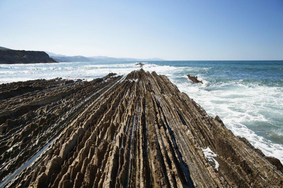 La ruta del Flysch, que discurre entre las localidades guipuzcoanas de Zumaia y Deba, y forma parte del Geoparque de la Costa Vasca, pasa por ser unas de las más bonitas del País Vasco. Tanto que estas impresionantes formaciones de origen sedimentario que se adentran en el mar, como rocas aradas por un rastrillo gigante, aparecen en la séptima temporada de la serie 'Juego de Tronos'. Se pueden disfrutar en barco o en una caminata senderista que solo es posible cuando la marea está baja.