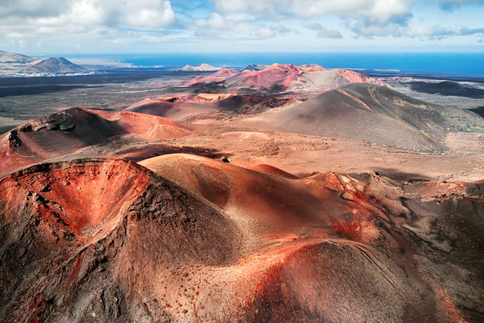 El parque nacional de Timanfaya, en Lanzarote, está formado por numerosas estructuras geomorfológicas, de gran interés para los vulcanólogos, surgidas de las erupciones ocurridas entre 1730 y 1736, y en 1824. El paisaje volcánico manda en el único parque nacional español eminentemente geológico. Rojos, pardos, ocres, negros, naranjas y nada de verde, debido a la ausencia de vegetación, sobre formas rugosas y la silueta de más de 25 volcanes. Y la costa abrupta con el mar de fondo.
