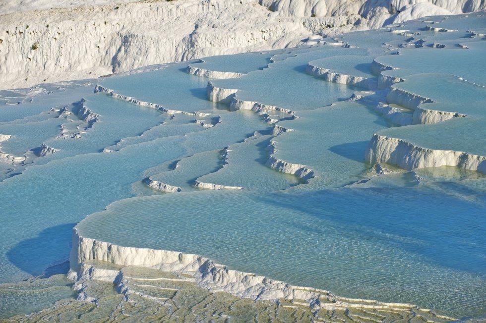 """""""Pamukkale"""" significa en turco """"castillo de algodón"""" y da nombre a un blanco entramado de piscinas naturales de aguas termales, dispuestas en terrazas de piedra caliza y travertino que bajan, como cascadas petrificadas, por la ladera de una montaña. Esta famosa atracción se sitúa en la provincia de Denizli, en el suroeste de Turquía, y se salvó al ser declarada patrimonio mundial por la Unesco: había comenzado a ser invadida por hoteles que destruyeron parte de los restos de la antigua ciudad de Hierápolis, y estaba asolada por un turismo irresponsable. Los hoteles han sido demolidos, la rampa de asfalto construida a modo de acceso se ha cubierto de pozas artificiales donde darse un baño y está prohibido el uso de zapatos al pisar tanta blancura."""