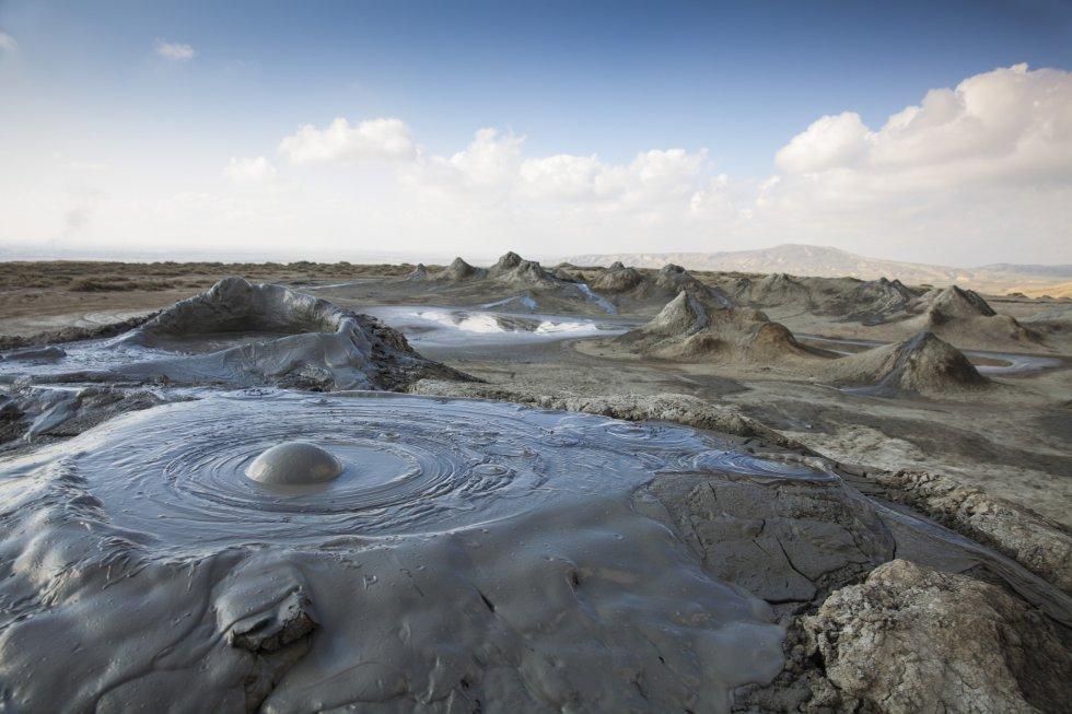 Un volcán de lodo es más pequeño que uno de lava, y se produce por la excreción de gases y líquidos que se encuentran en el subsuelo, por debajo de una capa arcillosa, y de agua. Todo esto es empujado hacia la superficie, formando un cráter con una laguna de lodo a la que acuden a rebozarse viajeros que creen en sus propiedades medicinales. Los expertos estiman que 300 de los alrededor de 700 volcanes de lodo que se calcula que hay en todo el planeta se encuentran en el parque nacional de Gobustán, junto al Mar Caspio. Con ejemplos notables como los cráteres Firuz, Gobustán, Salyan, Boyuk Khanizadagh y Turaghai (que figuran entre los más grandes del mundo) o Lokbatan, considerado uno de los más activos.