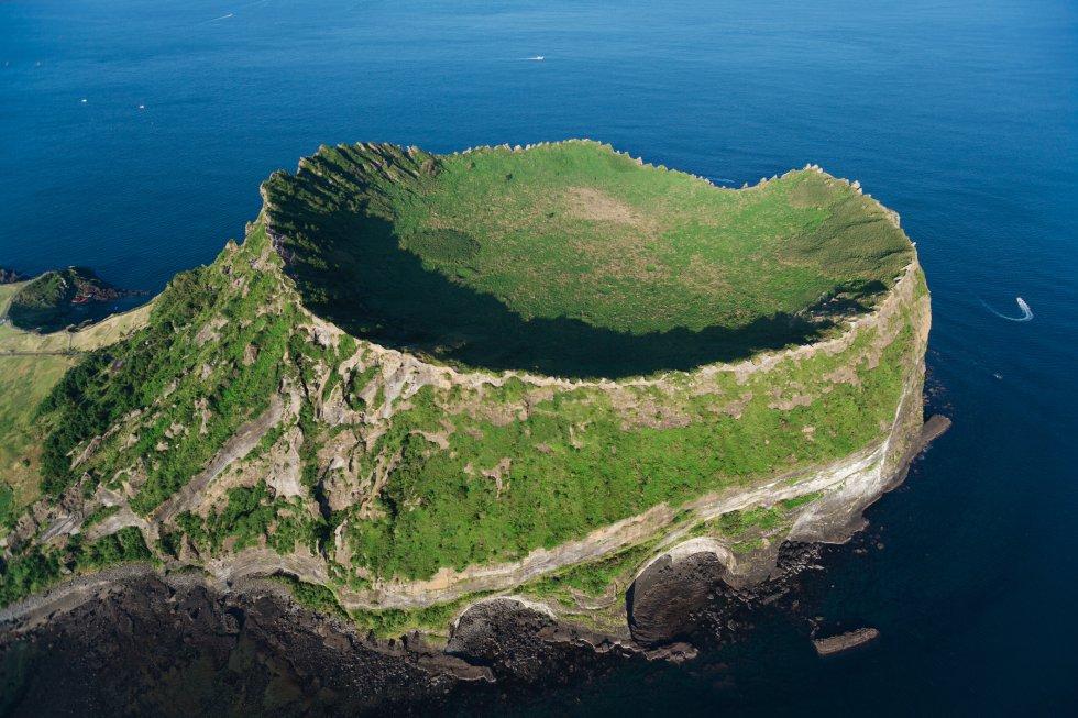 El paisaje volcánico y los túneles de lava de la isla de Jeju, en el suroeste de Corea del Sur, ha hecho triplete en la Unesco: patrimonio mundial, geoparque global y reserva de la biosfera. Abarca tres áreas diferenciadas que suman casi 19.000 hectáreas, algo más de una décima parte de la superficie de la isla: el Geomunoreum, uno de los sistemas de grutas formadas por túneles de lava más bellas del mundo, donde las oscuras paredes de lava contrastan con multicolores techos y suelos carbonatados; el cono de tuf de Seongsan Ilchulbong (pico del Amanecer, en la foto), una espectacular fortaleza que surge de las aguas del océano, y el monte Hallasan, la cumbre más alta del país, con cascadas, formaciones rocosas y un lago en su cráter.