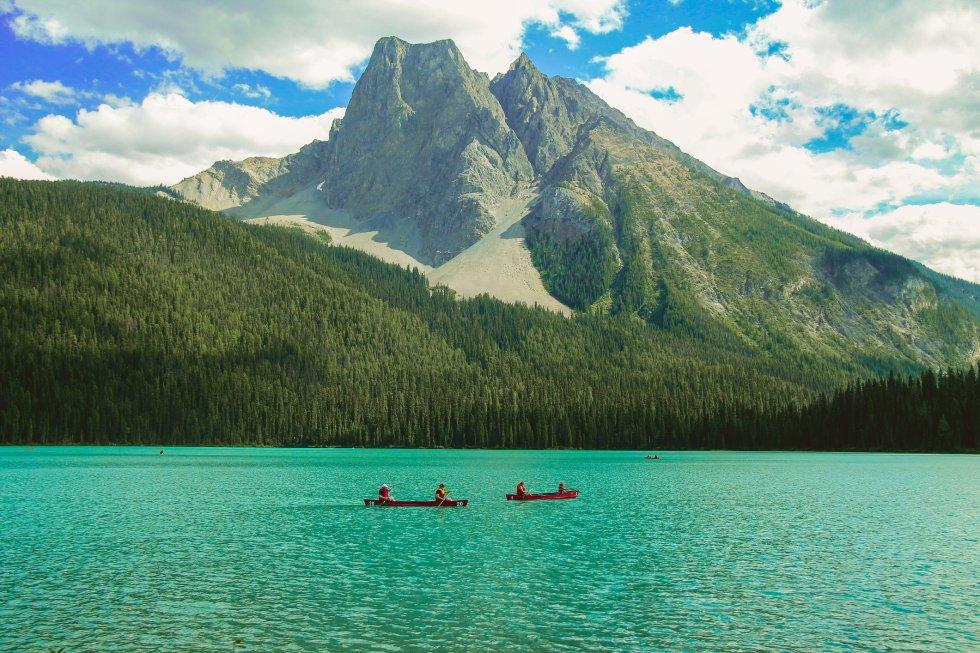 """El espectacular Esmeralda, flanqueado por bosque y dominado por picos nevados, es un buen epítome de lago de alta montaña. Se sitúa en el parque nacional Yoho de Canadá, en la Columbia Británica, a unos 1.300 metros de altitud, rodeado de la cordillera President –integrada en las de las Montañas Rocosas–, Wapta y el monte Burgess. Cuando el guía canadiense Tom Wilson lo descubrió accidentalmente en 1882 confesó que se quedó sentado en su caballo disfrutando de """"la rara y pacífica belleza del paisaje"""". Debe su color esmeralda a finas partículas de sedimento glacial suspendidas en el agua. Agua que se congela de noviembre a junio y se puede bordear mediante una ruta senderista de poco más de cinco kilómetros."""