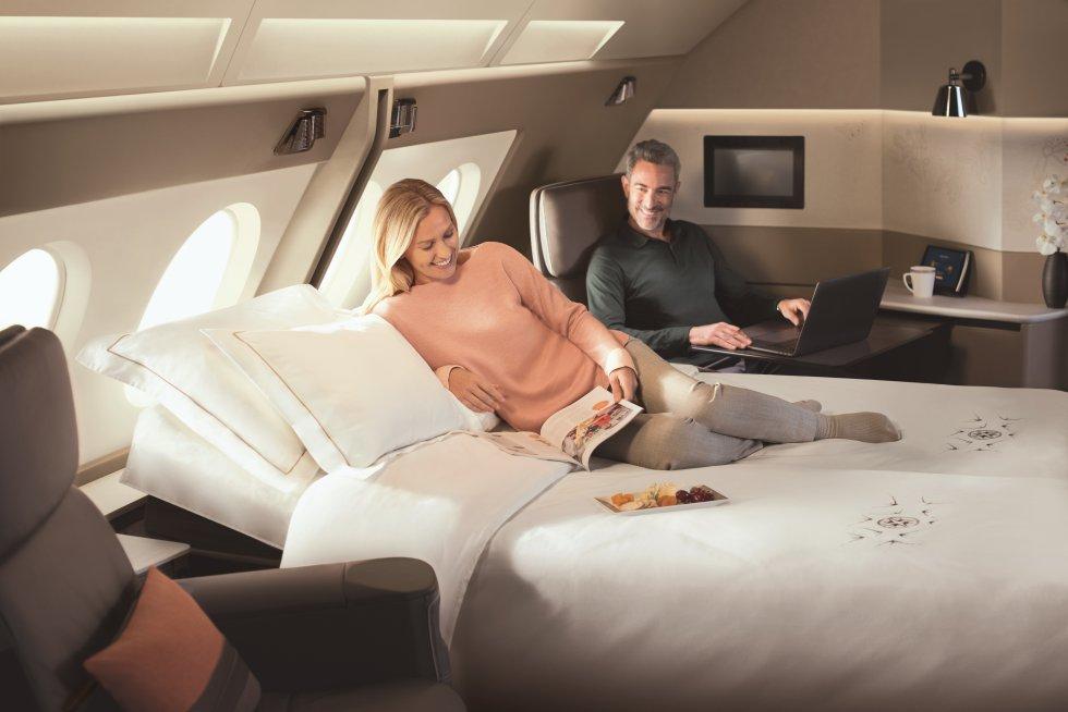 """A las cabinas de primera clase, Singapore Airlines las llama """"suites"""". Algo que uno entiende al ver las comodidades que tiene el pasajero que viaja en alguna de las ocho habitaciones de sus aviones B777-300ER. Además de la privacidad que otorga a los viajeros tener puertas y persianas en su cabina individual, en el espacio hay un sillón de piel reclinable y también una cama. Además, cuando la cama no se está utilizando puede ser guardada o convertida en un sofá. Como en la imagen, algunas de las 'suites', diseñadas por Jean-Jacques Coste (especializado en yates de lujo), se pueden unir para quienes viajan acompañados."""
