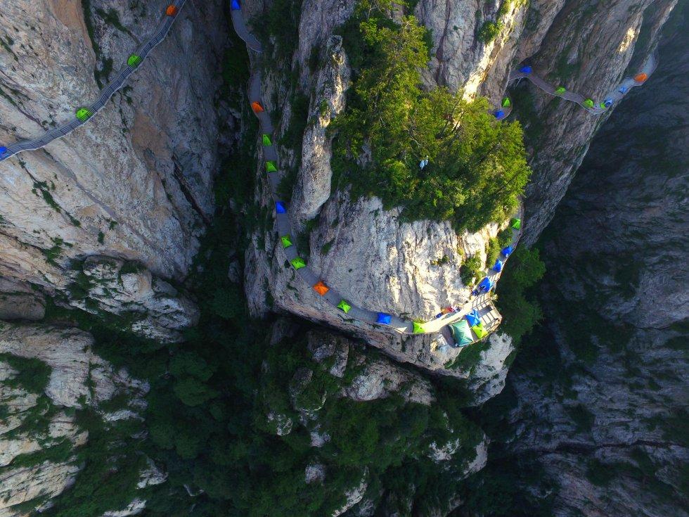 Não é uma imagem comum, nem mesmo aqui, na montanha chinesa de Laojun, na província de Yunnan, no sul da China. Durante uma noite no final de julho, os participantes de um festival de caminhadas dormiram sobre um trecho da passarela —de mais de dois quilômetros de comprimento na sua totalidade— que acompanha os paredões rochosos. Acima, o céu. Mil metros abaixo, o fundo de um vale arborizado. Uma centena de barracas pintaram com suas cores vivas o cinza do corte vertical e deram origem a espetaculares fotos aéreas. O momento chave da experiência foi o amanhecer, quando os primeiros raios do sol dissolvem o mar de nuvens que circundam a montanha. Além de ser um lugar sagrado para os taoístas, o parque Laojun é conhecido por sua rica biodiversidade, incluindo um décimo dos rododendros do planeta.