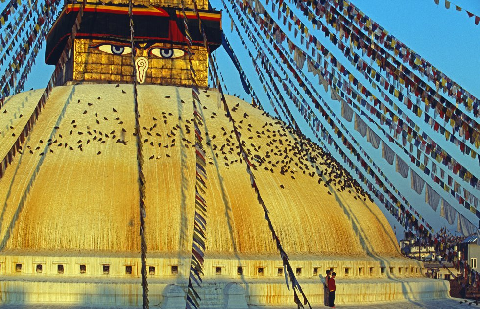 Boudhanath, o epicentro da comunidade budista tibetana no Nepal, tem uma das maiores e mais antigas estupas (600 d. C) do vale de Kathmandu. Sua espetacular cúpula branca, encimada por uma torre dourada, foi reconstruída após o terremoto de 2015. Sob os grandes olhos de Buda, monges e peregrinos realizam o ritual do kora, girando ao redor da estupa enquanto recitam mantras.