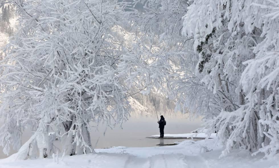 """Embora nesse dia o termômetro marcasse 16 graus abaixo de zero e atingisse -32 segundo o autor da foto, o frio não parece afugentar o pescador da imagem, feita em 10 de dezembro na margem do rio Ienissei, nas proximidades da cidade russa de Krasnoyarsk (com pouco mais de um milhão de habitantes), uma das paradas da mítica ferrovia Transiberiana no coração da Sibéria. A camada branca que tão belamente cobre as árvores não é neve. É o sincelo, um fenômeno meteorológico (hidrometeoro) produzido quando a temperatura é muito baixa e a neblina envolve os pinheiros, abetos e bétulas formando delicadas plumas e agulhas de gelo sobre seus galhos. Uma paisagem branca e fria que o escritor Anton Tchekhov descreveu durante uma viagem pela Sibéria. """"O Ienissei, a taiga, as pousadas, os cocheiros, a natureza selvagem, a vida selvagem (...), tudo isso em seu conjunto é tão agradável que não posso descrever."""""""