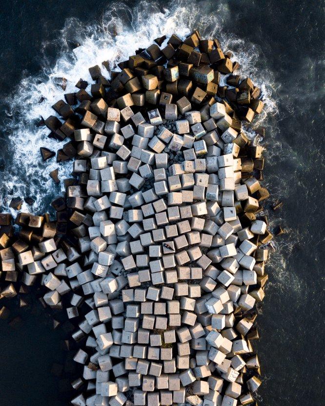 Márton Mogyorósy, un fotógrafo de 18 años especializado en arquitectura e imágenes aéreas, en medio de uno de los espigones de Barcelona.