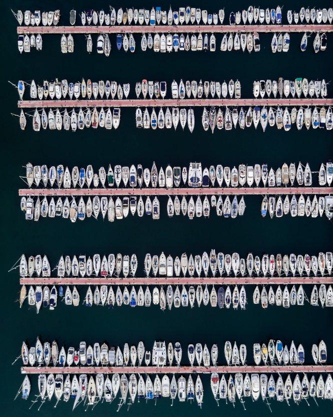 El concepto de simetría se transmite también con esta imagen de los barcos anclados en el Port Vell de Barcelona. Inaugurado en 1995, este lugar alejado del puerto de los grandes buques se integra perfectamente en la ciudad de Barcelona.