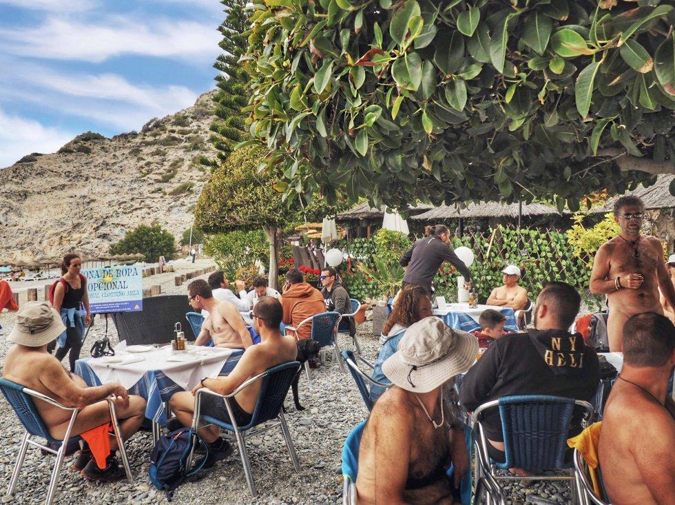 A la sombra del ficus de hoja pequeña se congregan las mesas del restaurante La Barraca donde la ropa es opcional. Playa de Cantarriján, Almuñécar (Granada).