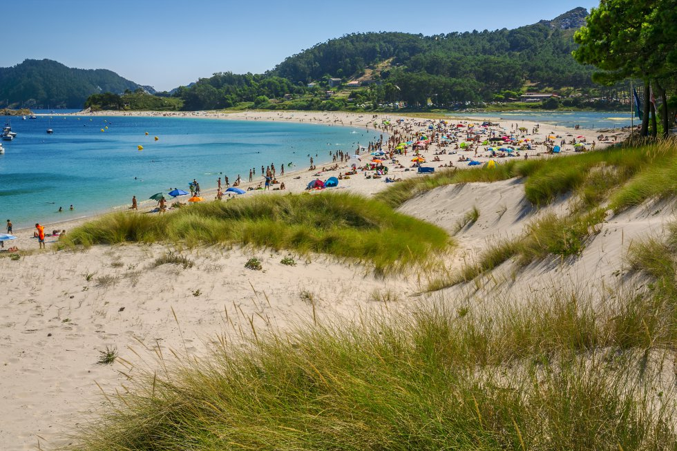 En 2007 el diario británico 'The Guardian' afirmó que Rodas era la mejor playa del mundo. Ahora los lectores de 'El Viajero' la han subido hasta el segundo puesto del ranking de las playas más bonitas de España. Y es que todo recuerda al Caribe en ese arenal de las islas Cíes, salvo por la gelidez de las aguas, claro. Rodas tiene arena de cal y aguas de vidrio, en ella ondea la bandera azul y desprende ese bienestar que produce estar en la cabecera de la ría de Vigo rodeados por el Atlántico. Haremos bien en no quedarnos amontonados junto al muelle donde llegan los barcos, sino espaciarnos por el cordón dunar, sin que afecte la acción violenta de las olas. Por la parte trasera, donde los pinos tienen las raíces al aire, se camina hasta la laguna, aunque la mejor panorámica de este istmo que empalma dos islas se obtiene desde el alto de la Campana, camino del faro. Para evitar saturaciones se precisa un permiso de la Xunta (previo a la compra de pasaje en barco que se obtiene en esta web: autorizacionillasatlanticas.xunta.gal ).