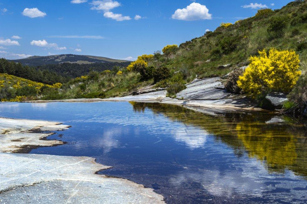"""Lagunas, gargantas, circos, riscos, galayos (agujas graníticas), depósitos morrénicos. Dominado todo por el imponente pico Almanzor, de 2.592 metros, techo del Sistema Central. El  parque regional Sierra de Gredos , en el sur de la provincia de Ávila, es, como señala Turismo de Castilla y León, """"un espacio tallado por la erosión glacial"""" en el que destacan el Circo y la Laguna Grande de Gredos. En su vertiente sur hace calor, aunque hay pozas en las que refrescarse; en la norte (la zona de Hoyos del Espino, por ejemplo), el viajero tiene prácticamente garantizado dormir con manta.   En la imagen, la garganta de Valdeascas, en la sierra de Gredos."""