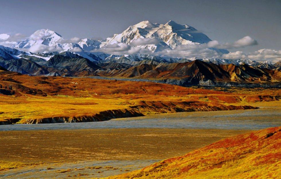 """La montaña más alta de América del Norte (6.190 metros sobre el nivel del mar) ha vuelto a llamarse Denali (""""El Grande"""" en lengua indígena), su nombre original, después de ser rebautizada como Monte McKinley y mantenerse con esa denominación hasta 2015, justo antes de que el por entonces presidente estadounidense Barack Obama visitara Alaska.  Todo este entorno de la cordillera de Alaska , en el centro-sur del Estado, está protegido bajo la figura de parque nacional y reserva Denali, que cada año recibe a unos 40.000 visitantes; en torno a 800 (dato de 2017) se registran para ascender la montaña, con una tasa de éxito del 60%."""